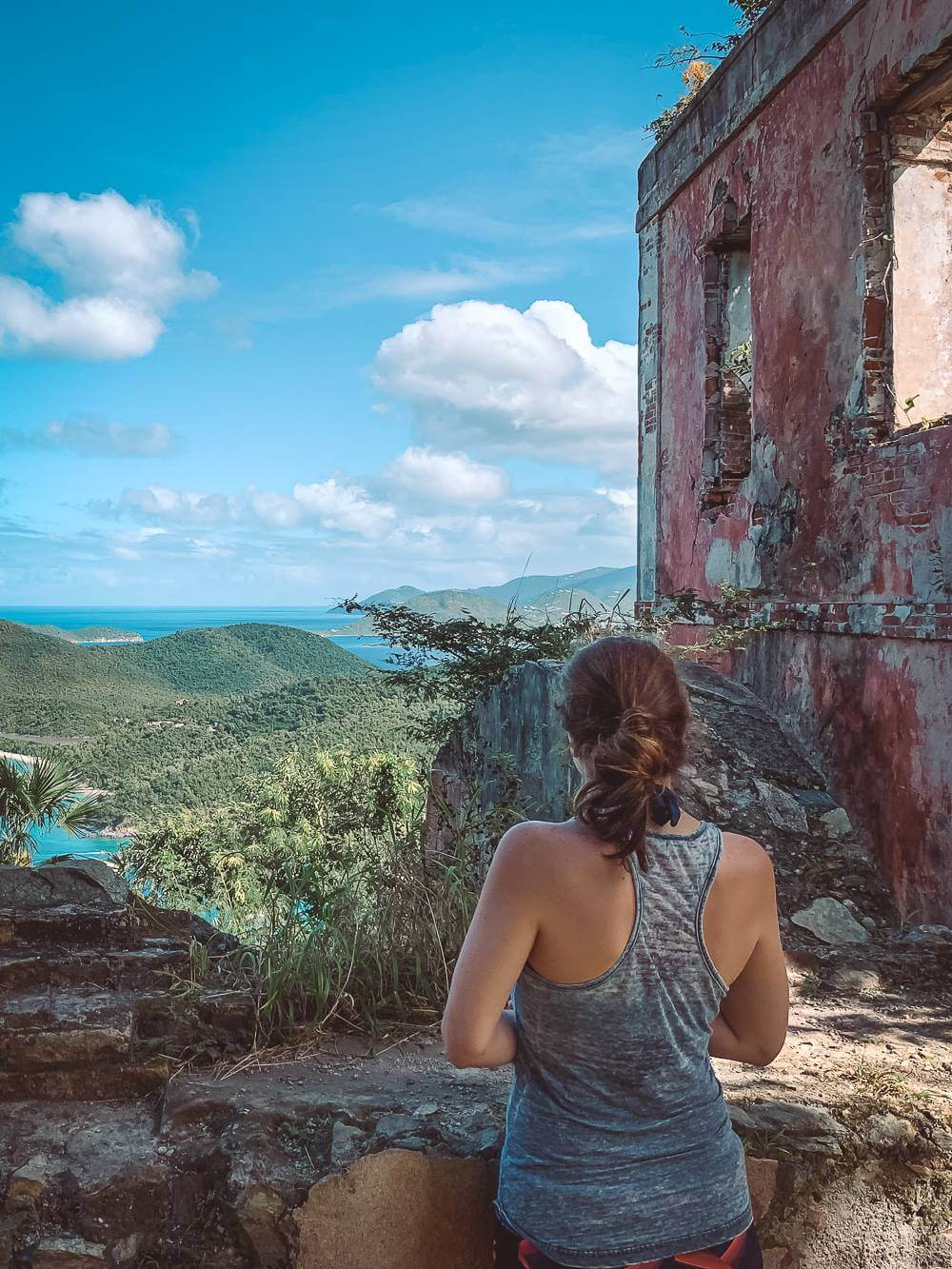 brunette girl in tank top next to plantation ruin overlooking Maho Bay